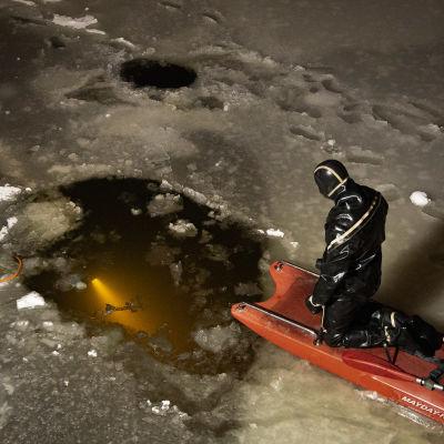 Sukeltaja odottaa avannon reunalla pelastustehtävässä olevaa sukeltajaa palaavaksi.
