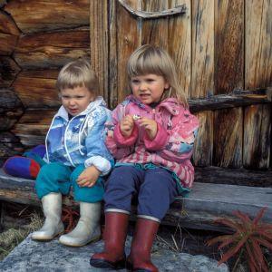 Pikkupoika ja pikkutyttö istuvat penkillä.