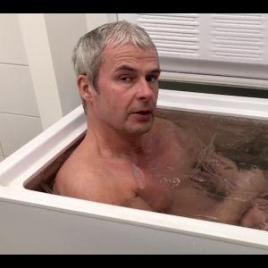 Yogaläraren Magnus Appelberg sitter i en frysbox fylld med is och vatten