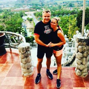 Pariskunta hymyilee portailla Thaimaassa.