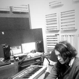 Artisten Chikiss sitter i rum fullt av synthar och skärmar och gör musik. Mörkt hår, hänger ner, Ansiktet i halvbild.