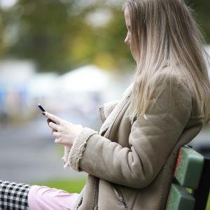 Anonyymi nainen istuu penkillä