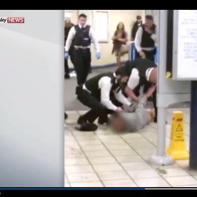 Kuvankaappaus Sky Newsin julkaisemasta silminnäkijän videosta, jossa poliisi taltuttaa metroasemalla puukon kanssa ohikulkijoiden kimppuun hyökänneen miehen.