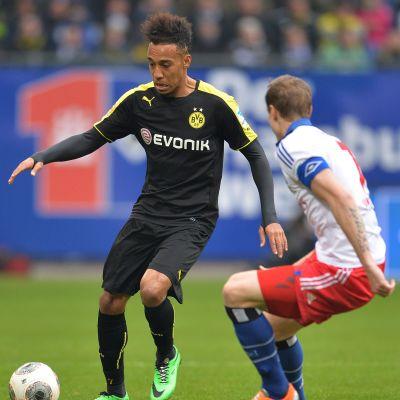 Dortmundin Pierre-Emerick Aubameyang yrittää harhauttaa HSV:n Marcell Jansenin.