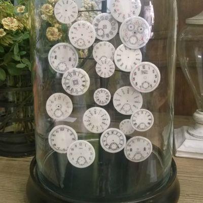 En glasklocka med gamla urtavlor i.