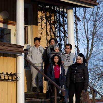 Afganistanilainen, turvapaikan saanut Azimin perhe kotitalonsa portailla Kyyjärvellä.
