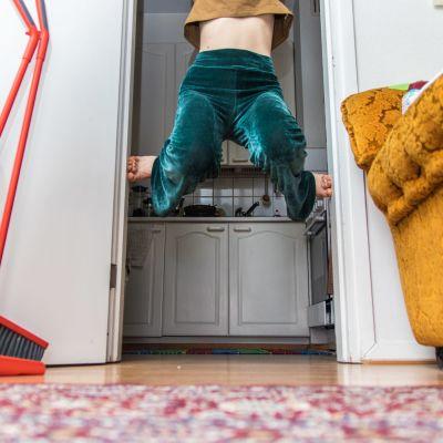 Kvinna klättrar i dörröppning.