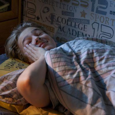 Teini-ikäinen poika herää aamulla sängyssään.