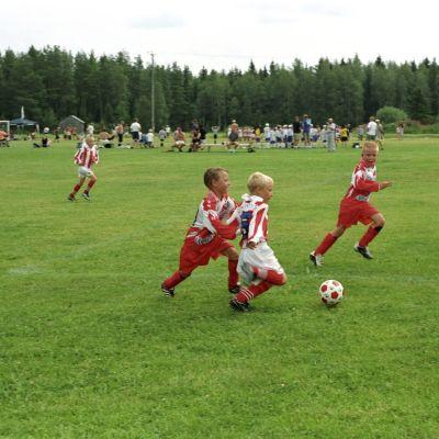 Kolme pikkupoikaa pelitilanteessa kentällä.
