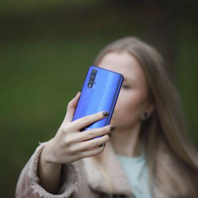 Valokuvat ovat someajan kauppatavaraa, jolla saadaan näkyvyyttä ja lisää seuraajia. Nuori nainen ottamassa selfietä.