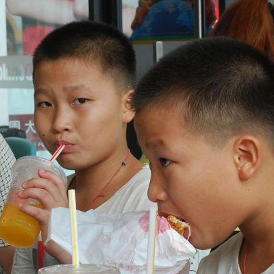 Ah-hei (till vänster) och hans bror äter hamburgare på en snabbmatsrestaurang.