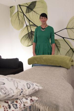 En kvinna med kort svart hår, och grön klänning, står vid en bänk som har kuddar och filtar på sig.