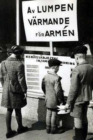 Lapset seisovat näyteikkunan edessä katsomassa ilmoitusta lumppukeräyksestä huhtikuussa 1942.