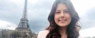 En kvinna med långt brunt hår som befinner sig i Paris. I bakgrunden syns  Eiffeltornet 3700f5b7ce7c7