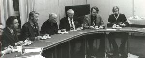 Sex personer sitter vid ett mötesbord