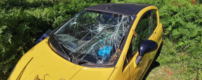 en gul mopedbil med sprucken vindruta.