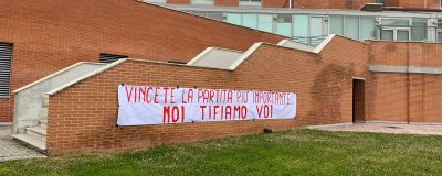"""En tegelbyggnad med en banderoll där det står """"Vinn den viktigast matchen, vi hejar på er"""" på italienska."""