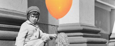 En liten flicka med en ballong och en majvippa sitter på domkyrkans trappor i Helsingfors 01.05.1966.