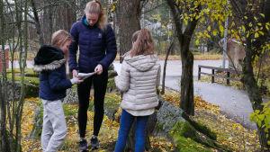 kolme lasta tekee koulutehtäviä ulkona