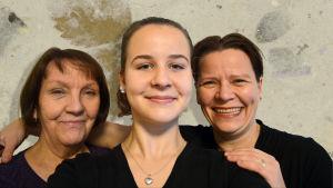 Kolme eri-ikäistä naista mustissa vaatteissa hymyilee ja katsoo suoraan kameraan.