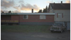 """Pickup-auto ränsistyneen talon alapihalla. Talon katonrajassa lukee """"kukkakauppa""""."""
