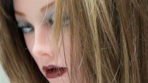 Kvinnlig perukmodell med sandfärgad peruk.