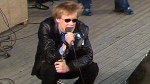 Martti Syrjä istuu kyykyssä lavalla Kemut-konsertissa Tampereen Särkänniemessä.