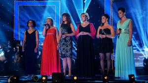 Naiset laulavat lavalla