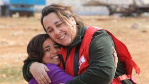 röda kors-arbetare kramar om liten flicka