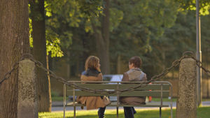 Nuorempi ja vanhempi nainen istuu vierekkäin puistonpenkillä.