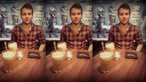 Andreas Höglund sitter i ett kafé med en kaffe framför sig.