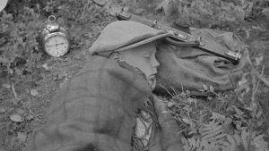 Kannakselainen poika on ponnistellut ahkerasti evakuoimispuuhassa ja nyt uinahtaa hetkisen matkalaukku päänalaisenaan. Herätyskellon hän on asettanut viereensä, jotta hän olisi lähtöhetkellä valmis. Noitermaa 1944.