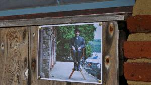 Foto av skådespelaren David Suchet som Hercule Poirot fäst i båthusväggen i Greenway.