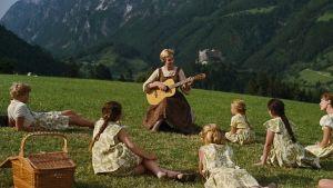 Bild ur filmen The Sound of Music. Maria spelar gitarr och sjunger för barnen i en alpsluttning.