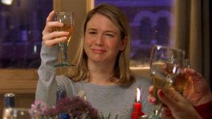 Bild på Bridget Jones som håller upp ett glas.