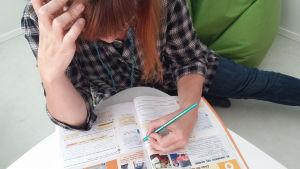 Nainen lukee oppikirjaa kynä kädessä