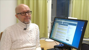 Jan Wickman sitter vid sin dator i arbetsrummet på Åbo Akademi.
