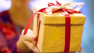 Nainen pitelee käsissään joulupakettia