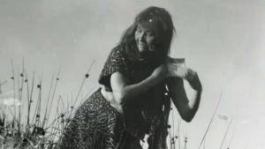 Stenålderskvinna kammar sitt hår.