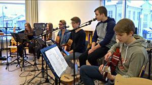 elever spelar gitarr och sjunger