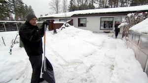 Seppo Lepistö nojaa lumikolaan takapihallaan.
