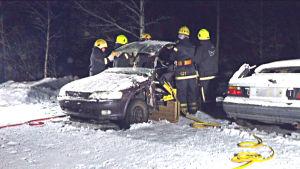 Frivilliga brandkårister skär av taket på en krockad bil.