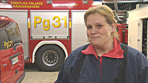 Kvinna framför brandbil i brandkårshuset i Pargas.