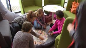 Fyra flickor spelar brädspel