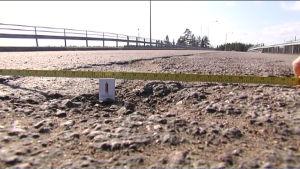 Tändstgicksask i och måttband över grop som har lappats med oljegrus på landsvägen mellan Lappträsk och Lovisa.