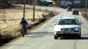 Bil kör om cyklande barn på smal landsväg.