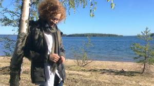 Saimi Hoyer nojaa koivuun järven rannalla