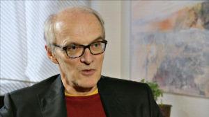 Professor i arbetsrätt, Seppo Koskinen i röd tröja och svart kavaj.