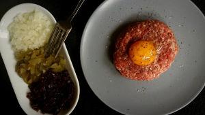Råbiff med äggula, saltgurka, lök och rödbeta.
