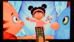 En hand som håller i en fjärrkontroll. I bakgrunden syns ett barnprogram på en teve.